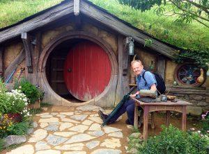 Vor der runden Tür einer Hobbithöhle.